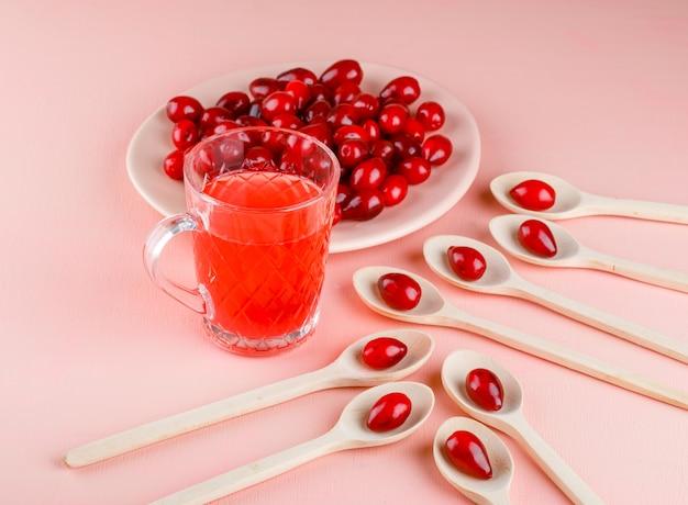 Baies de cornouiller avec boisson en assiette et cuillères en bois sur rose, high angle view.