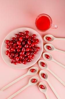 Baies de cornouiller avec boisson dans une assiette et cuillères en bois sur rose, vue de dessus.