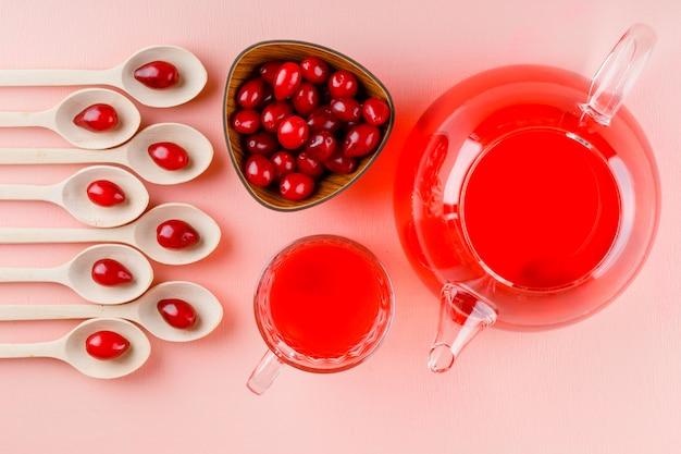 Baies de cornouiller avec des boissons dans des cuillères en bois et bol sur rose.