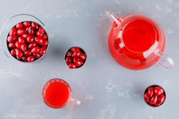 Baies de cornouiller dans des mini seaux avec boisson sur plâtre