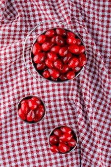 Baies de cornouiller dans des mini seaux sur toile de pique-nique. vue de dessus.