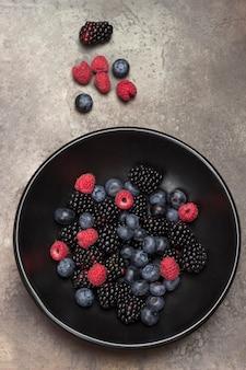 Baies dans une assiette en céramique noire: mûre, cerise, myrtille et framboise. surface grise. concept de perte de poids. mise à plat