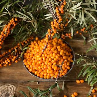 Baies fraîches d'argousier sur une assiette vintage. branches éparses et baies d'argousier