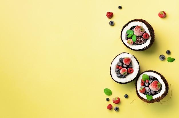 Baies fraîches biologiques, feuilles de menthe à l'intérieur de noix de coco mûres. la moitié de la noix de coco dans un style plat minimal.