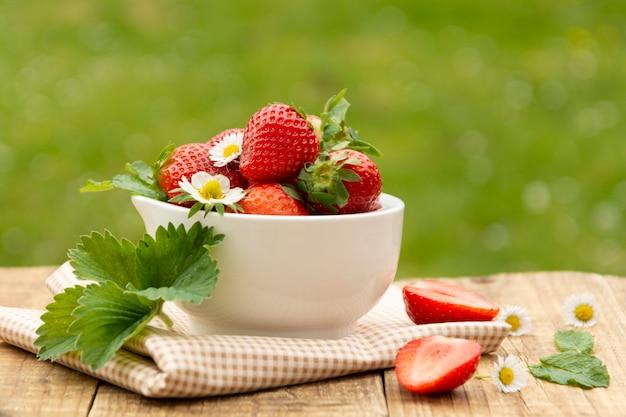 Baies fraîches d'été. fraises isolés sur fond d'herbe verte, lumière du jour