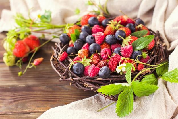 Baies fraîches fraises framboises et myrtilles sur fond de bois aliments sains superaliments...