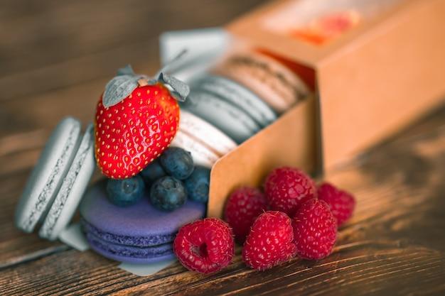 Baies fraîches de myrtilles, framboises et fraises, à côté de biscuits macarons