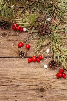 Baies fraîches de rose de chien, bonbons en boule, branches et pommes de pin, neige artificielle. décorations nature, planches en bois vintage