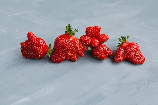 Baies de fraises drôles. nourriture à la mode. manger des fruits et légumes laids.