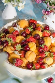 Baies et fruits frais mûrs - abricots, fraises, cerises dans une assiette avec des gouttes d'eau sur fond bleu