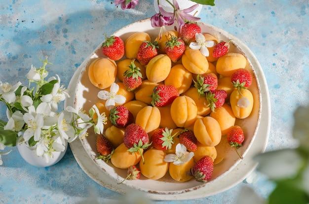 Baies et fruits frais mûrs - abricots, fraises dans une assiette sur fond bleu