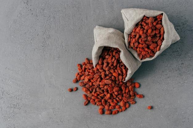 Les baies de goji en bonne santé se sont répandues hors du petit sac, isolé sur fond gris.