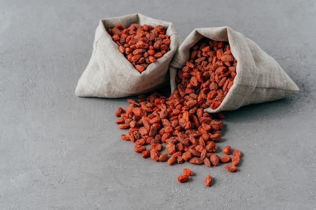 Baies de goji organiques crues rouges dans de petits sacs rustiques et étalées sur fond gris.