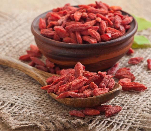 Baies de goji séchées rouges dans une cuillère en bois