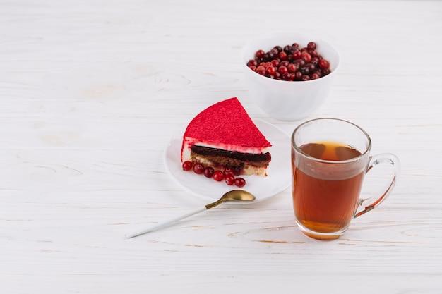 Baies de groseilles biologiques brutes et tranches de gâteau avec une tasse de thé aux herbes