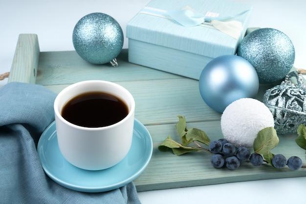 Baies d'hiver sur une branche avec une boîte-cadeau, une tasse de café et des boules de noël sur un plateau bleu doux