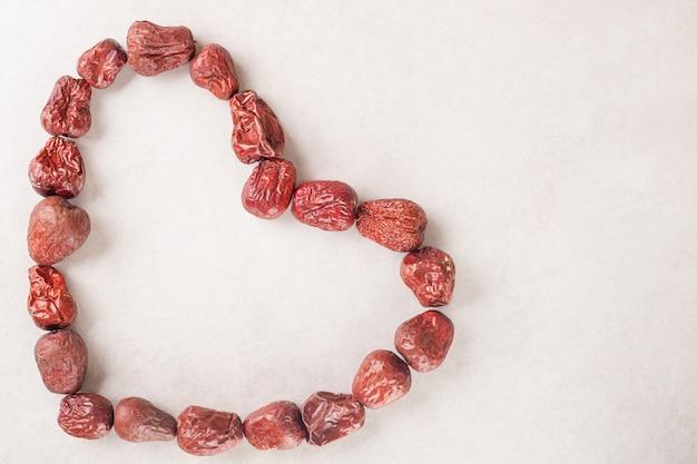 Baies de jujube séchées en forme de coeur sur du béton.