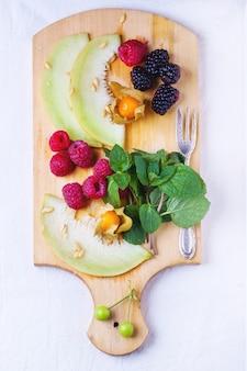 Baies, menthe et melon sur planche à découper en bois