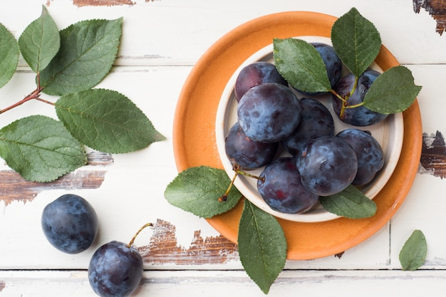 Baies de prunes fraîches sur une assiette avec des feuilles