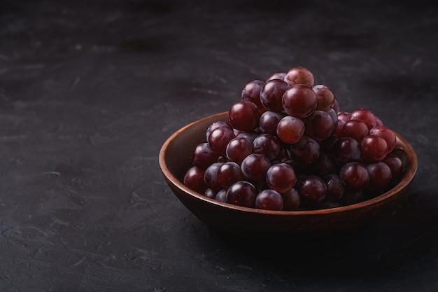 Baies de raisin mûres fraîches dans un bol en bois brun sur une surface en pierre sombre, vue d'angle