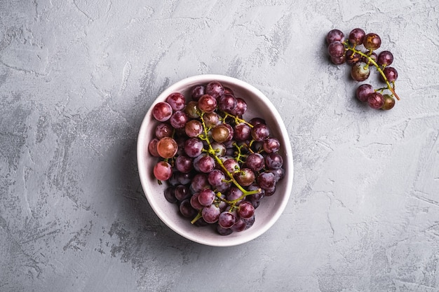 Les baies de raisin mûres fraîches dans un bol sur du béton en pierre