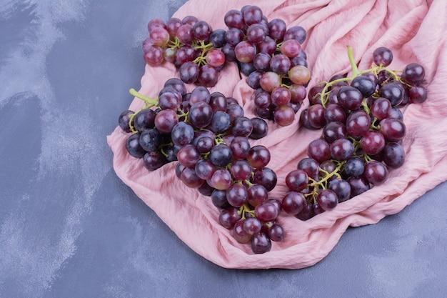 Baies de raisin rouges isolés sur une surface bleue