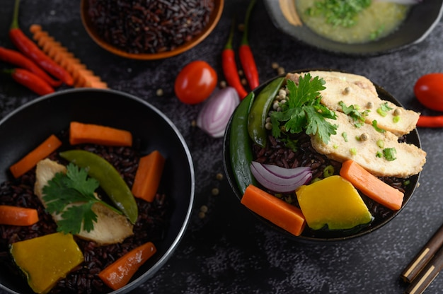 Baies de riz pourpre cuites avec du blanc de poulet grillé. citrouille, carottes et feuilles de menthe dans un plat, aliments propres.