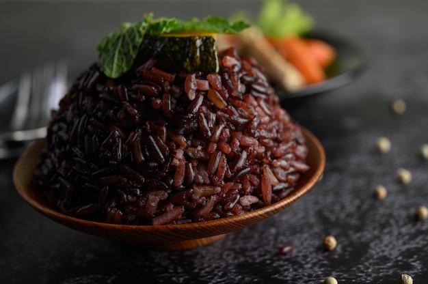 Baies de riz violet cuites dans un plat en bois avec des feuilles de menthe.