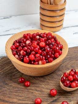 Baies rouges de mûres dans un bol en bois sur une table blanche