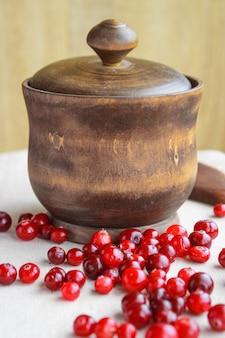 Baies rouges et un pot en bois sur la table
