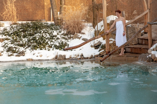 Baignade de jeune femme dans un lac gelé après le sauna