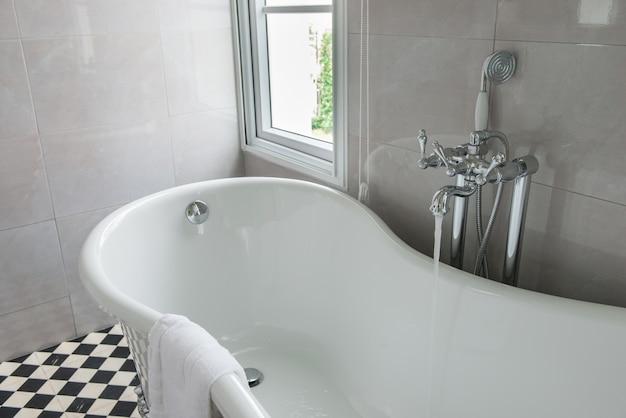 Baignoire luxueuse dans une salle de bain moderne, vue sur les vitres latérales, lumière du soleil, journée ensoleillée