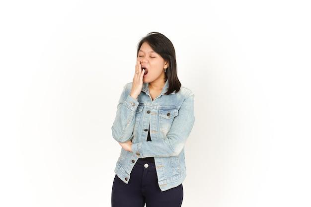 Le bâillement de beautiful asian woman wearing jeans jacket et chemise noire isolé sur fond blanc