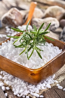 Bain de sel dans un bol en bois avec du romarin
