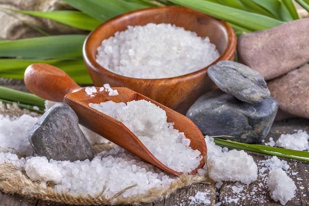 Bain de sel dans un bol en bois avec des feuilles de bambou en arrière-plan