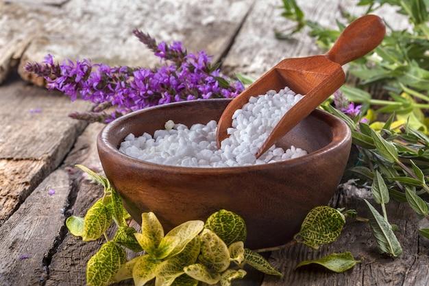 Bain de sel dans un bol en bois avec des fleurs et des feuilles en arrière-plan