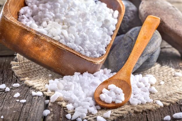 Bain de sel dans un bol en bois sur la vieille table en bois