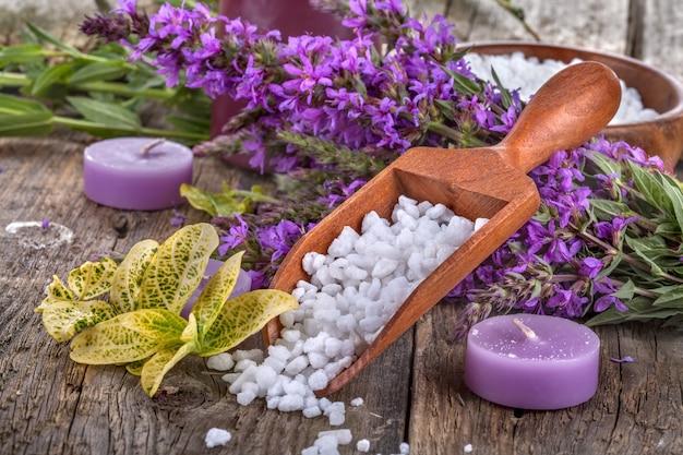 Bain de sel dans une cuillère en bois avec des fleurs et des feuilles en arrière-plan