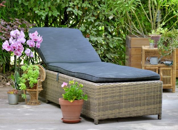 Un bain de soleil en osier sur une terrasse en bois pour se détendre dans son jardin