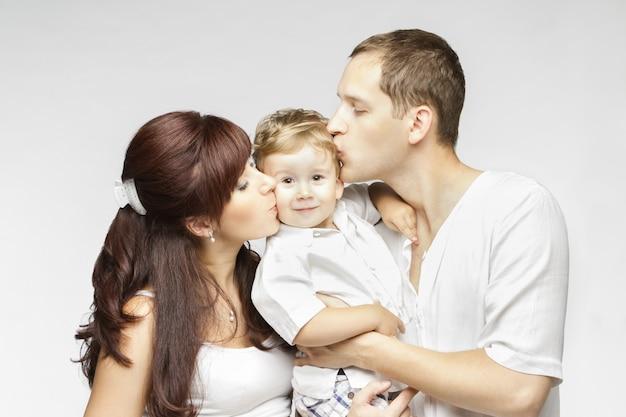 Baiser de famille, mère père embrassant enfant, parents et fils de deux ans