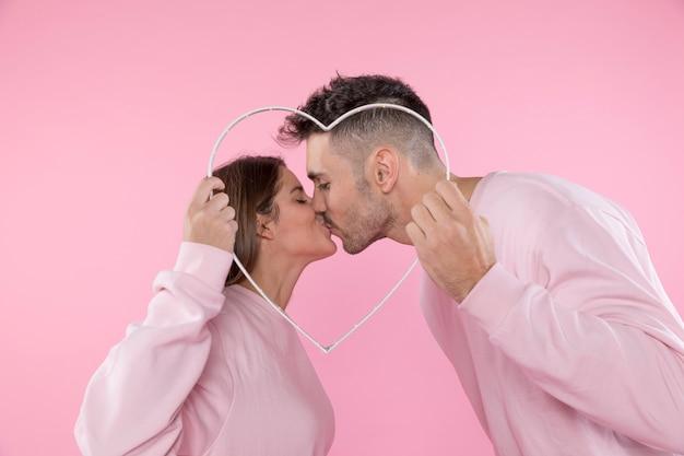 Baiser de l'homme et de la femme tenant le symbole du coeur