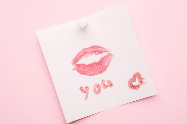 Un baiser de rouge à lèvres imprimé sur un morceau de papier. fond pastel rose.