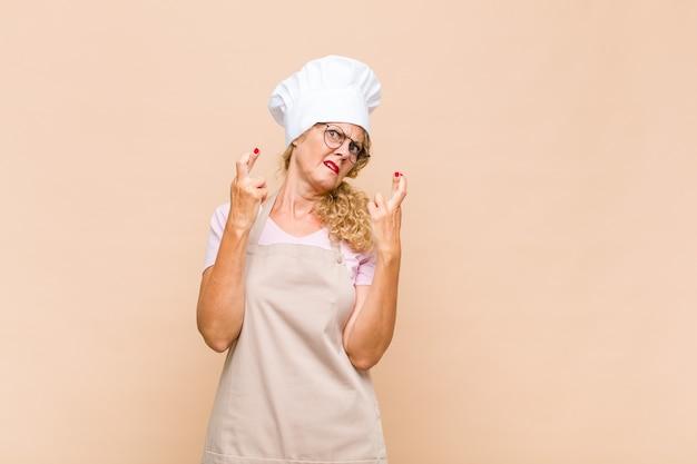 Baker femme d'âge moyen croisant les doigts avec anxiété et espérant avoir de la chance avec un regard inquiet