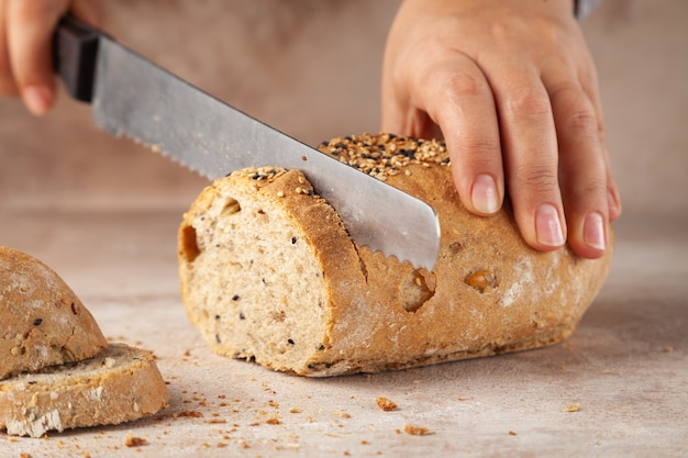 Baker mains, hacher du pain aux céréales avec un couteau, des tranches sur une planche à découper en bois, concept de petit-déjeuner, horizontal, copiez l'espace, place pour le texte