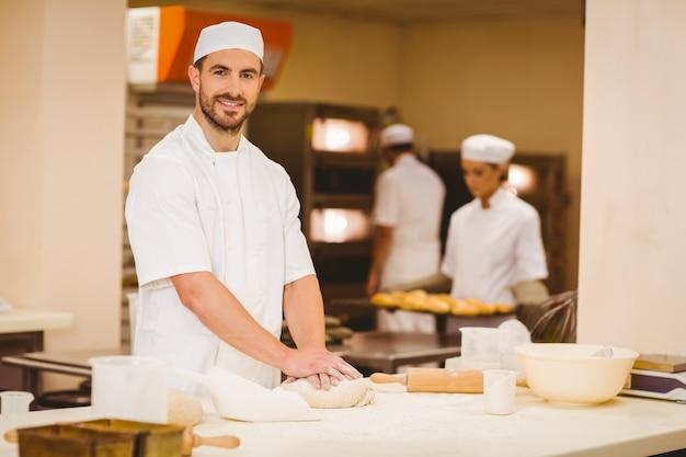 Baker pétrir la pâte à un comptoir