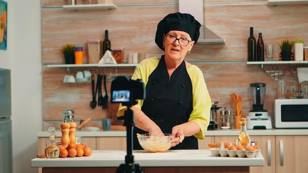 Baker portant un podcast d'enregistrement de bonete d'une recette de cuisine traditionnelle utilisant de la farine et des œufs fêlés. chef influenceur utilisant la technologie internet communiquant, tirant sur les médias sociaux avec un équipement numérique