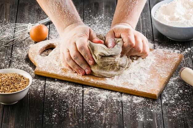 Baker's main en train de pétrir la pâte avec de la farine sur une planche à découper