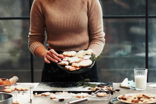 Baker tenant le plat avec des biscuits en pain d'épice