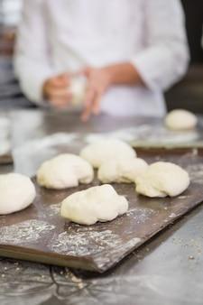 Baker en train de pétrir une pâte non cuite sur le plan de travail