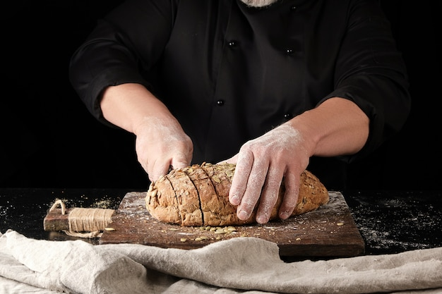 Baker en uniforme noir coupe un couteau en tranches de pain de seigle